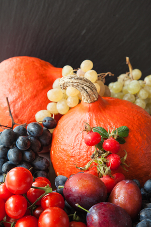 Assortment of autumn fruits and vegetables on black background