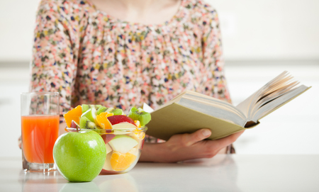 Unrecognizable young woman reading a book and having fruit lunch