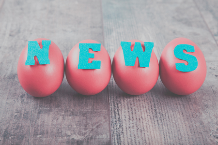 News factory: four eggs with news word on wooden background