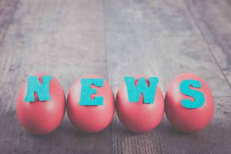News factory: four eggs with news word on wooden background, copy space
