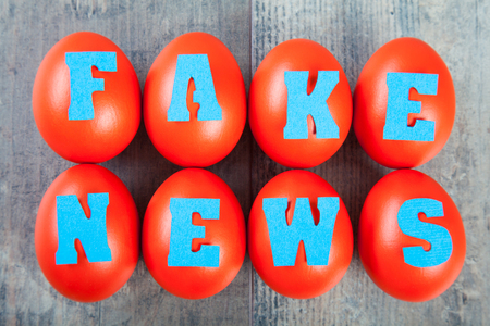 Factory of fake news: eggs with fake news words on wooden background Stock fotó