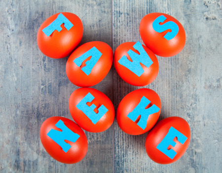 Fake news factory: eggs with fake news words on wooden background