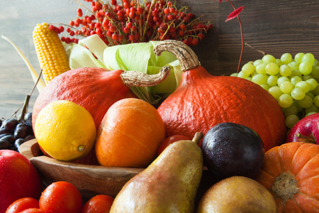 Autumn harvest: plenty of fruits and vegetables on wooden background