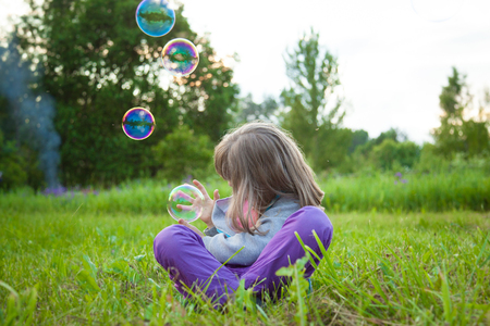 Unrecognizable little girl playing with soap bubbles sitting on the grass Stock fotó