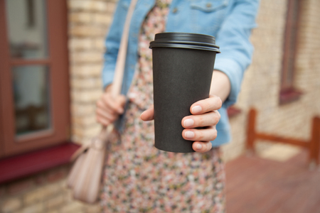 Unrecognizable young woman with a cup of coffee outdoors Stock fotó