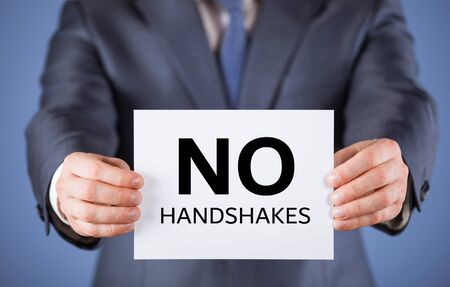 Unrecognizable businessman reminds to avoid handshakes