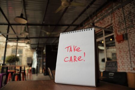 Take care text written on a paper on the street cafe table Фото со стока
