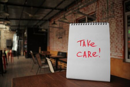 Take care text written on a paper on the street cafe table