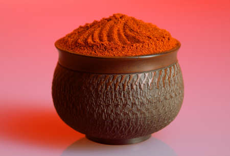 Red pepper powder in a beautiful bowl, red background