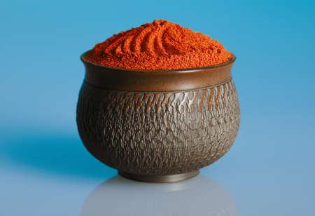 Red pepper powder in a beautiful bowl, blue background