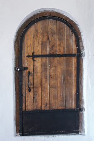 old wooden door with a ferrous mount in a white wall Stok Fotoğraf