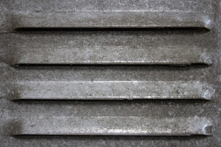 Dust-laden vent opening on an old ferrous closet 版權商用圖片