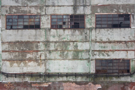 Windows and wall of the old neglected industrial building Stock Photo