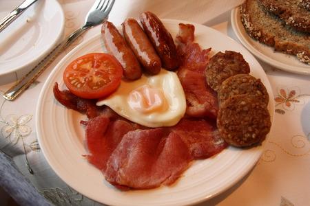 traditional irish breakfast on large plate.  bacon, sausage, tomato, egg photo