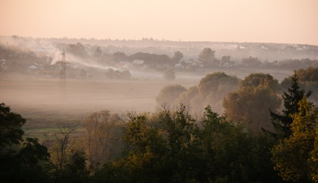 summer with fog and smoke and sun over village photo