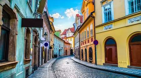 Street in Prague with old houses and road of paving stone at sunrise