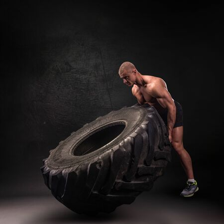 Sportsman lifting heavy wheel