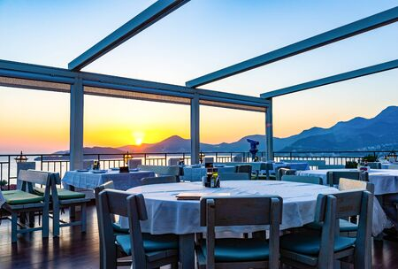 Romantic cafe on terrace with the view on mountains and beautiful sunset over Adriatic sea, Montenegro