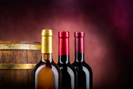 Three bottles of wine and wooden barrel on a burgundy background Imagens