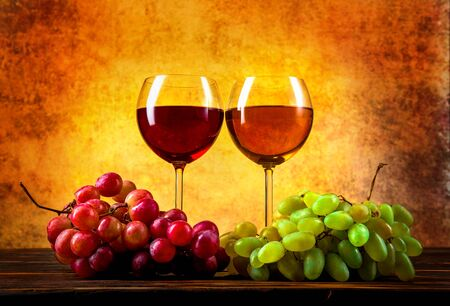 Wineglasses and grape on table Imagens