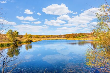 Reflection of clouds in calm river in autumn countryside