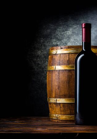 Bottle of red wine and wooden barrel on a black background