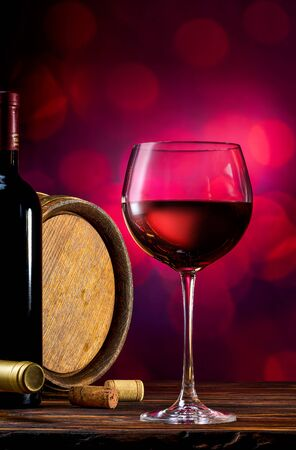 Red wine and wooden barrel on a burgundy bokeh background