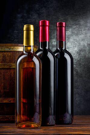 Three bottles of wine near wooden barrel in cellar Imagens