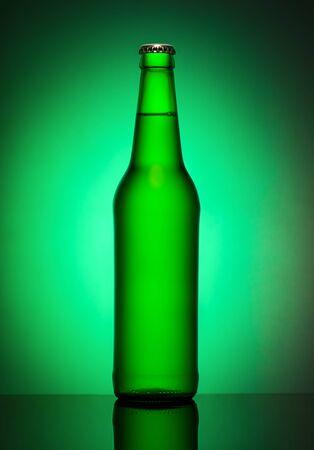 Matte bottle of beer on a green background