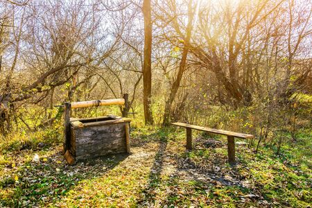 Old wooden well-draw and bench in autumn forest Imagens