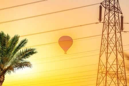 Hot balloon in he yellow sky of Egypt at sunrise