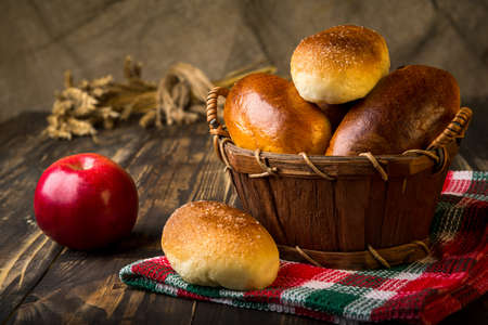 Baked apple pies in basket on wooden table Banco de Imagens
