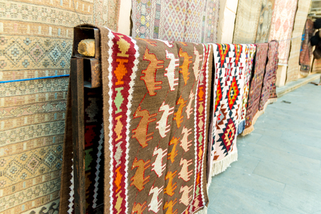 Group of precious ancient colored wool Azeri ancient carpets made by hand in ancient city at Carpet store. Stock Photo