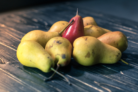 Group of ripe pears on dark rustic wooden table.