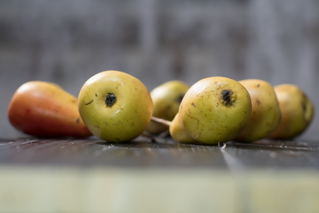 Group of ripe pears on dark rustic wooden table. Side view horizontal shot. Empty copyspace for your design.