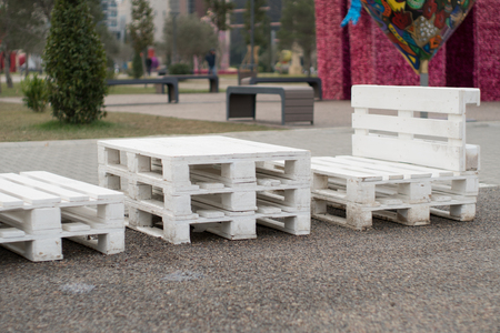 Wooden bench made of pallets of freight cargo cases for sitting. Creative outdoor cafe table and benches.