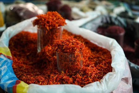 Saffron at bazar in sacks and measure glass cup. Close up shot.