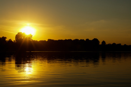 A beautiful orange and yellow sunset on a river. Horizontal image. An evening sun is reflected in the water like a road to the skies. Water is almost still with no wind.