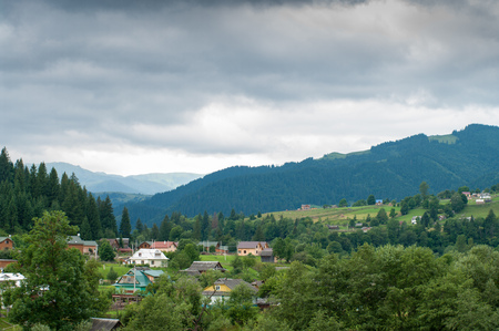 Clouds have gathered over a mountain village in Carpahia. Houses are surrounded by trees. A nice place for recreation and holidays in Ukraine. Stock Photo