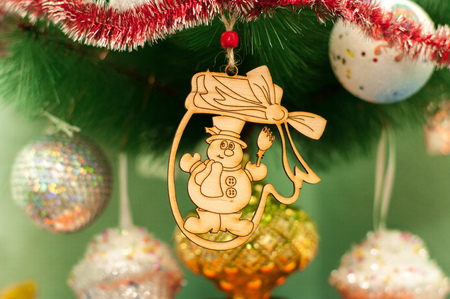 A handmade wooden toy for a fir tree. New Year and Christmas time celebration. Surrounded with shiny decorative balls. Stock Photo