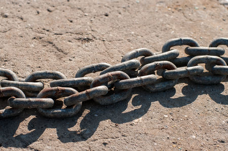 A metal chains on the naval pier. Steel is covered with rust. Located on a concrete basement.