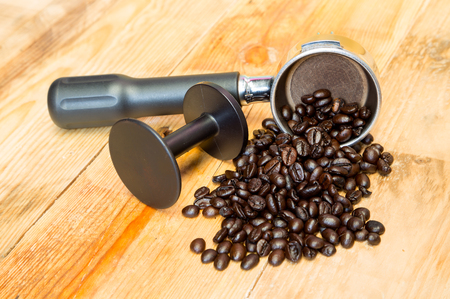 tamper: An espresso machine group head and coffee beans with tamper. Stock Photo