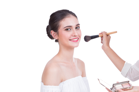 Beautiful young lady with bright make-up and brushes on white background