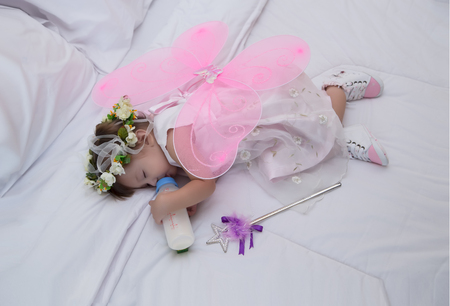 Little girl wearing dresses pink with angel wings, sleeping, eating milk on a white bed.