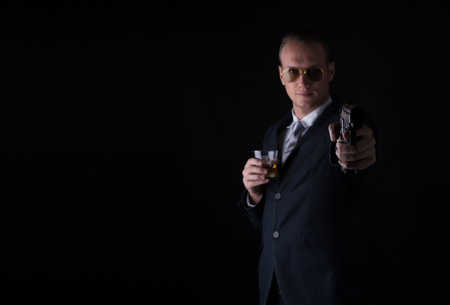 Handsome man in a suit aim with gun and whiskey on black background,focus on the gun.