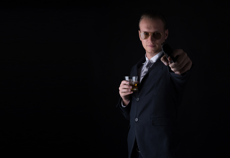 Cool man in a suit aim with gun and whiskey on black background.
