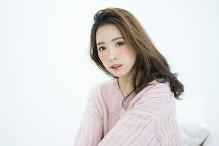 Winter portrait of young beautiful brunette woman wearing knitted sweater pink cold sitting in white room as background.Model fashion shooting. Autumn, winter season.