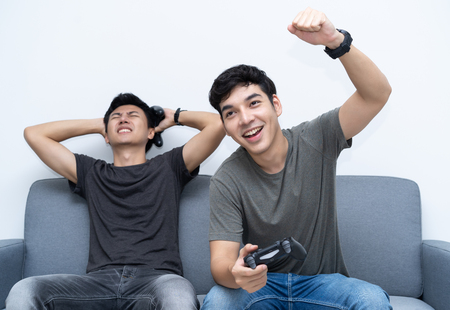 Friends and video games. Two young men gamer playing video games while sitting on sofa. One guy is celebrating winning. Foto de archivo