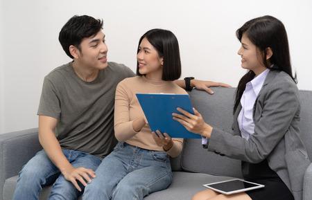 Makler bieten das Haus und zeigen Details zum Kundenpaar mit Immobilienmakler, der Haus zum Verkauf besucht Standard-Bild