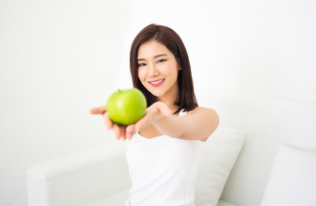 Positive of a beautiful Asian girl holding an apple sitting on sofa in white room